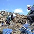 宮城県女川町のがれき集積場で、選別作業にあたる地元の若者たち。 仮設住宅に住む人々は毎日、こうしたがれきの山の前を通らなければならない。 (2012年6月、市川撮影)。