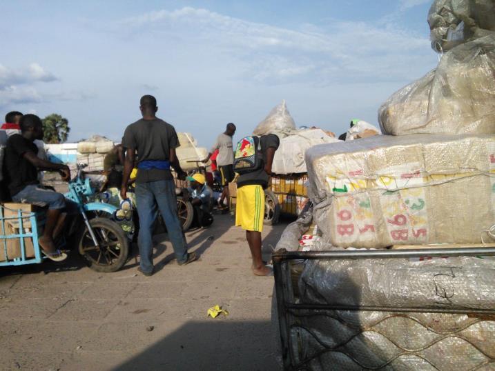 朝8時に港にやってきた障害者団体のメンバーは、夕方の16時過ぎまで随時キンシャサから運搬される荷物を各々の運搬用の車いすに積んでいく。最終便が到着して全ての梱包が終わると、団体代表が関税申告書(一枚につき約8米ドル)を支払い、まとめて輸入品の関税手続きをおこなう。(2013年11月22日、筆者撮影)