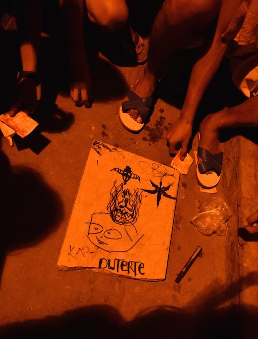 覚醒剤をきめて夜明けまでコイン賭博に興じる若者たち。ゲーム板には、ドゥテルテの名、大麻、キリストの姿などが描かれている。