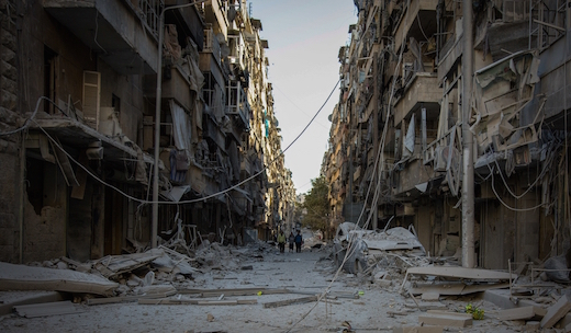 People walk down a street in Bustan Al Kasr neighbourhood after it was hit by airstrikes in mid-October 2016.© KARAM ALMASRI/MSF