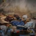 ゴミのなかで祈りを捧げる男性