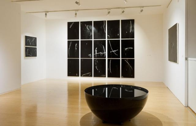 「目をあけたまま閉じる」会場風景(2011年) 光沢のある画面に指の跡が残る油彩画と、墨のインスタレーション 写真:長塚秀人 提供:アートフロントギャラリー アートフロントギャラリー「目をあけたまま閉じる」より