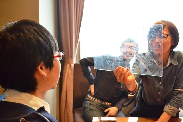 岡部さんのヘルパーさんに文字盤をかざされる小山さん