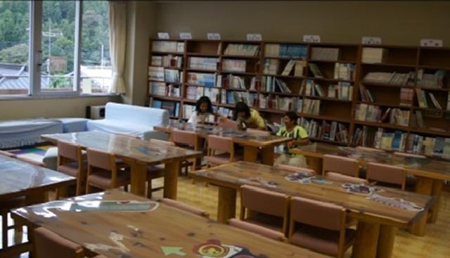 (写真3 休み時間の図書室:本棚の前に避難する子ども達(小学校C))