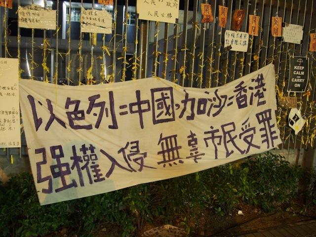 「イスラエル=中国、ガザ=香港」と訴える、政府庁舎前の広場の柵に掲げ られた横断幕(撮影:倉田明子)