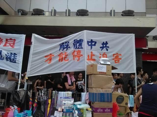 「中国共産党が解体しなければ迫害は終わらない」の横断幕を掲げたデモ参加者