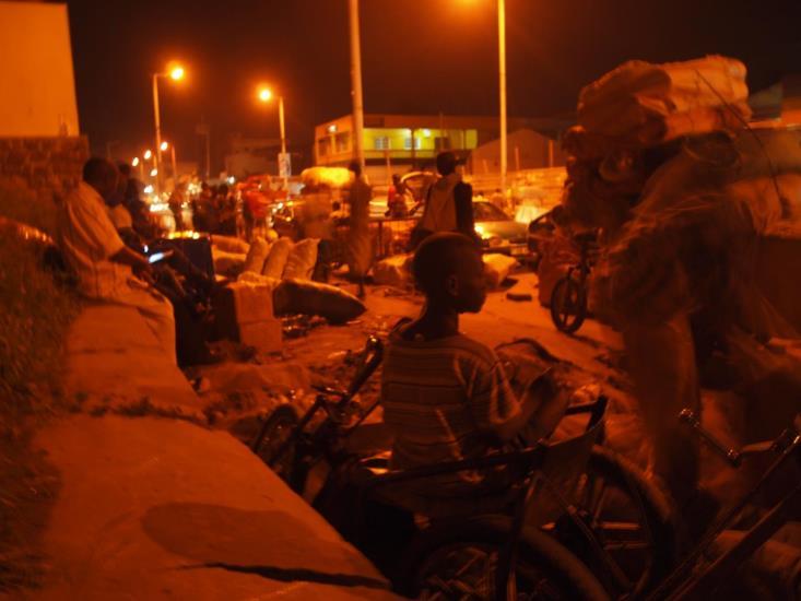 18時になると、障害者はそれぞれの介助者に運搬を手伝ってもらい、港から約1.5キロメートル離れた街中までやってきて、取引先と商品の受け渡しをおこなう。そして、20時半を回ったころにやっと1日の仕事を終え、タクシーや乗り合いバス、車いすで帰宅する。(2013年11月22日、筆者撮影)