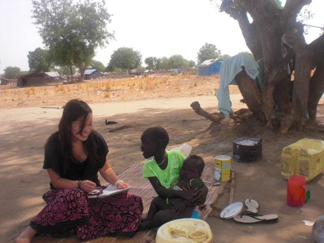 新しい家族のもとで暮らすニャディエン(仮名)、その「弟」と筆者。(2012年12月撮影)