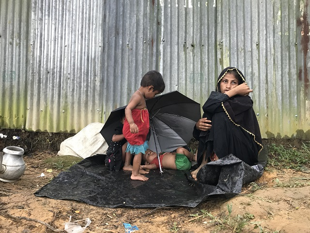 路上にすわりこむロヒンギャの母親 雨に濡れたビニールシートに子どもが寝ている