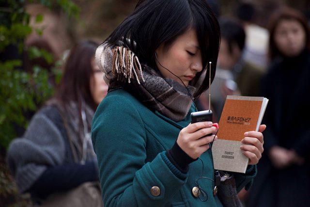 参加者はこんなふうにラジオとガイドブックを手にして町を歩くことになる。写真=蓮沼昌宏