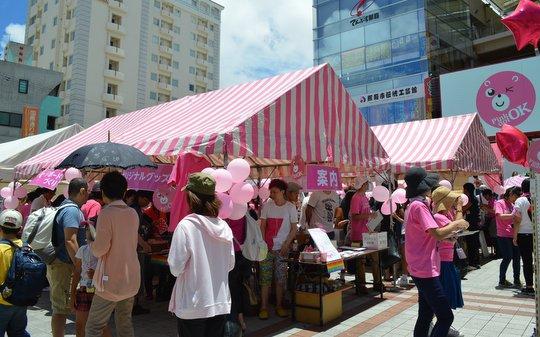 沖縄の眩しい陽射しの下、たくさんの人がピンク色を身に付けて集まる