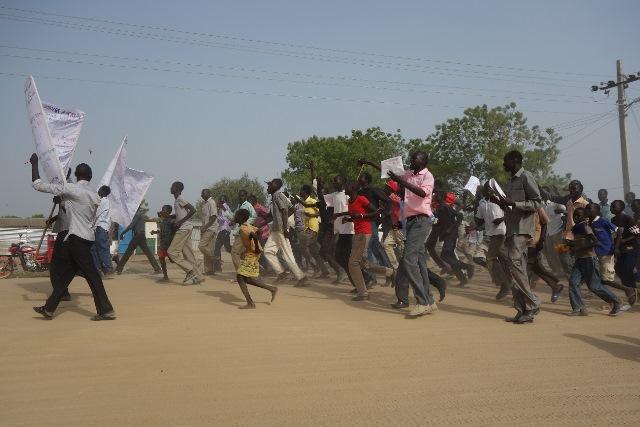 デモの様子。100人以上にもなるヌエルの若者は、政府の武装解除後の自分たちの集落の襲撃に対して、抗議のデモを行った。小さい子供も混ざっている。町中を疾走しながら行われるデモは、筆者もバイクでついていくのがやっとであった(2013年3月筆者撮影)