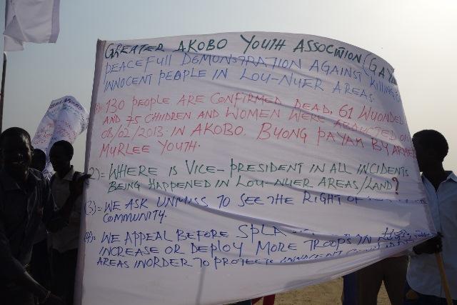 デモの際に掲げられた布。彼らの出身集落被害の状況と政府への不満が書かれている(2013年3月筆者撮影)
