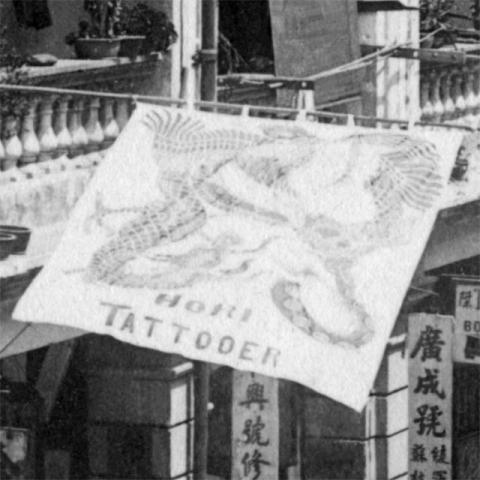 生田の店の旗の写真を拡大したところ、「HORI TATTOONER」と記されていることがわかった。(出典: c.1901 Queen's Road East http://gwulo.com/node/23059 )