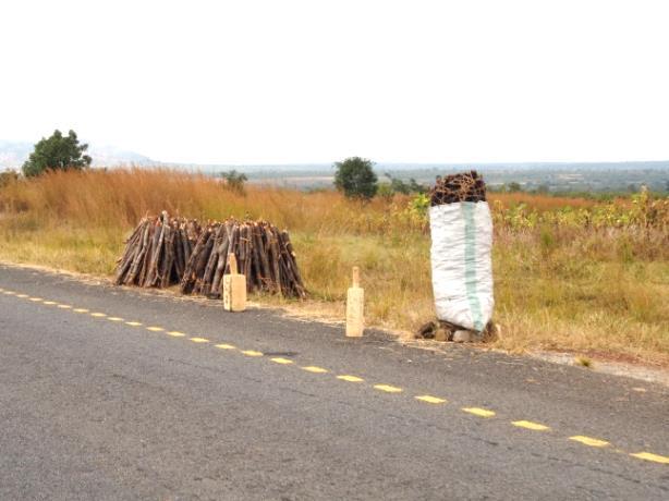 幹線道路沿いに並べられた薪炭と木製の車止め