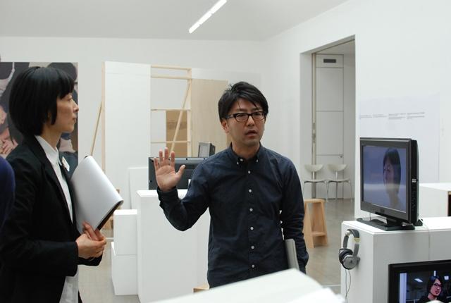 展示の説明をする田中功起さん。左は本展を企画した、水戸芸術館現代美術センター学芸員の竹久侑さん