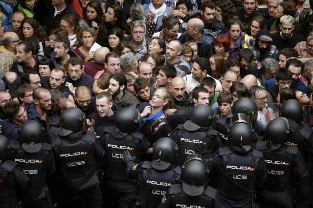 住民投票で国家警察ともみ合うバルセロナ市民  [エル・パイス紙、 2017年10月1日、Alberto Estévez, EFE]